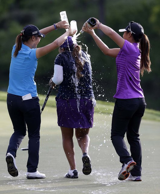 Lydia Ko, left, and Danielle Kang douse Lizette Salas, with sparkling wine and water as she celebrates winning the Kingsmill Championship golf tournament at the Kingsmill resort  in Williamsburg, Virginia, on May 18, 2014. Salas won her first LPGA event after shooting an even par-71 leaving her at 13-under for the tournament.  (Photo by Steve Helber/Associated Press)
