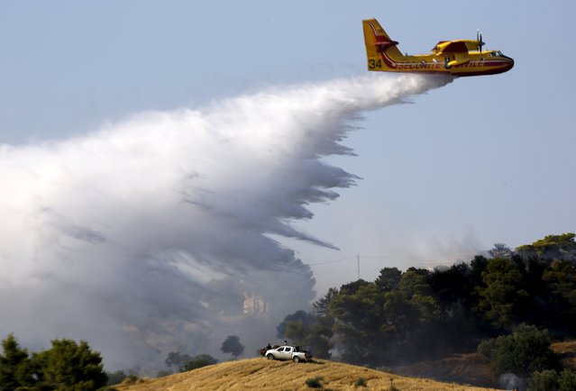 Locals watch as a firefighting plane drops water over a fire near holiday homes in Costa village in the Argolida region, in Southeastern Greece during a developing wild fire, July 20, 2015. Dozens of people were evacuated as firefighters fought the fire, which broke out on Monday afternoon in Panorama in Costa village at a forested area where dozens of summer houses are located, according to local media. (Photo by Yannis Behrakis/Reuters)