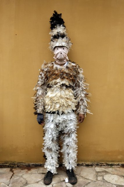 Alfredo Ortega poses for a photo in his bird-feather suit after attending a Mass commemorating the feast day of St. Francis Solano, in Emboscada, Paraguay, Friday, July 24, 2015. Paraguayan Catholics honored the Spanish friar also known as St. Francisco Solanus in a a mix of Indian and Catholic beliefs. The festival begins with a Mass, continues with a procession of the diminutive wooden statue of St. Francis, and ends with pledges covered in feathers from head to toe, dancing with fellow parishioners. (Photo by Jorge Saenz/AP Photo)