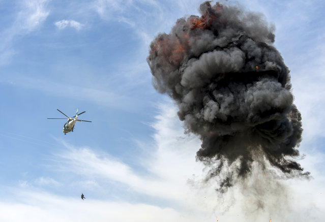 """Special forces perform a rescue effort with a EC 155 helicopter in the context of the event """"50 years of Police Helicopter Squadron Baden-Wuerttemberg"""" in Stuttgart, Germany, July 26, 2015. (Photo by Daniel Maurer/EPA)"""