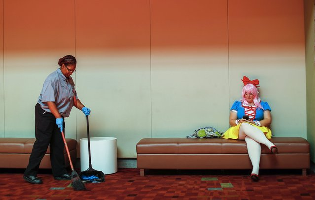 Georgia World Congress Center custodian Renita Pye (L) keeps the floor tidy as cosplayer Tamara Herndon (R) checks her mobile phone during the Momocon gaming and anime convention in Atlanta, Georgia, USA, 26 May 2017. The three-day gathering attracts fans of computer and video gaming, anime, cartoons and cosplay. Herndon is playing Super Sonico, a Japanese gaming character. (Photo by Erik S. Lesser/EPA)