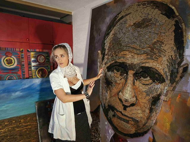 """Ukrainian artist Dariya Marchenko works at a portrait of Russian President Vladimir Putin named """"The Face of War"""" which is made out of 5,000 cartridges brought from the frontline in eastern Ukraine, in Kiev, July 23, 2015. (Photo by Gleb Garanich/Reuters)"""