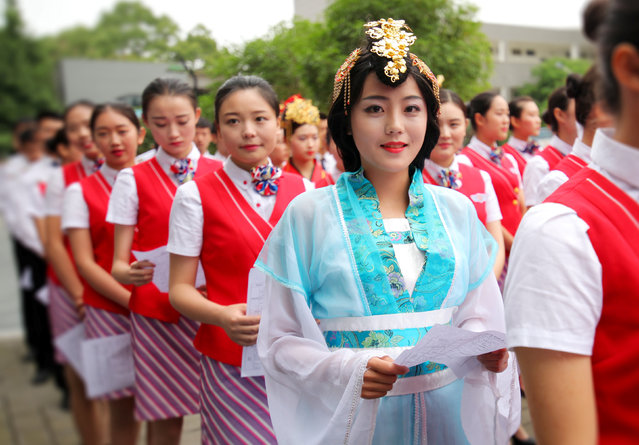 A student, wearing a traditional costume and headdress, stands in line for interviews during a recruitment held by an airline company, hoping to stand out from more than 500 candidates for airline stewardess positions, in Chengdu, Sichuan Province, China, May 27, 2016. (Photo by Reuters/Stringer)