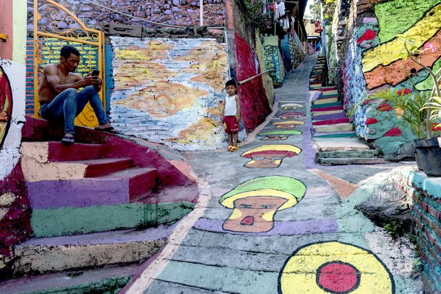 """This picture taken on May 23, 2017 shows villagers relax along a path at an Indonesian hamlet dubbed """"the rainbow village"""" in Semarang, central Java, that has become an internet sensation and attracting hordes of visitors. (Photo by Suryo Wibowo/AFP Photo)"""
