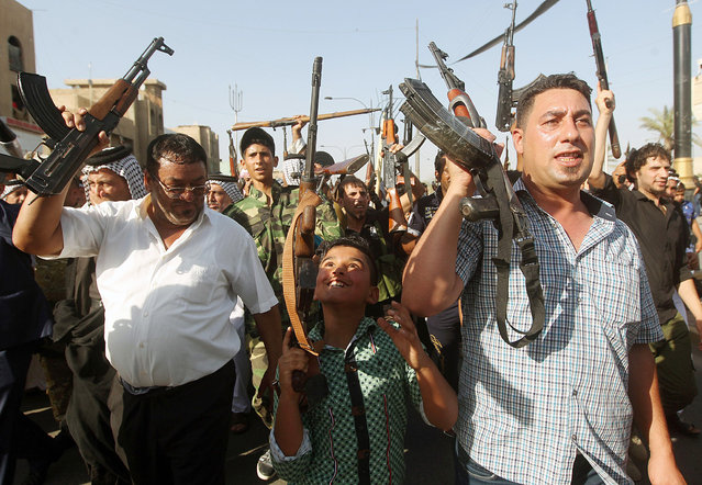 A Iraqi young boy and tribesmen hold up their weapons as they gather to show their readiness to join Iraqi security forces in the fight against Jihadist militants who have taken over several northern Iraqi cities on June 16, 2014 in the capital Baghdad. Faced with a militant offensive sweeping south toward Baghdad, Prime Minister Nuri al-Maliki announced the Iraqi government would arm and equip civilians who volunteer to fight, and thousands have signed up. (Photo by Ahmad Al-Rubaye/AFP Photo)