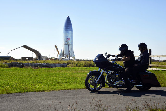 In this January 12, 2019 file photo, a motorcyclist rides near the SpaceX prototype Starship hopper at the Boca Chica Beach site in Texas. SpaceX says it will build its Mars spaceship in south Texas instead of the Port of Los Angeles, dealing another blow to the local economy only days after the company announced massive layoffs. The Southern California-based company announced Wednesday, January 16, 2019 that test versions of its Starship and Super Heavy rocket will be assembled at its Texas launch facility in a move to streamline operations. (Photo by Miguel Roberts/The Brownsville Herald via AP Photo)