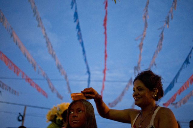 Leonor Blandon combs her son's hair, as he gets ready to participate in the celebration in honor of Santo Domingo de Guzman, Managua's patron saint, in Managua, Nicaragua, Saturday, August 1, 2015. The image of Santo Domingo was carried from his church in Las Sierritas, located south of the capital, on Thursday accompanied by parishioners to start the celebrations ahead of his Aug. 8 feast day. On August 10 he will be return to the same altar after the annual visit to the capital. (Photo by Esteban Felix/AP Photo)