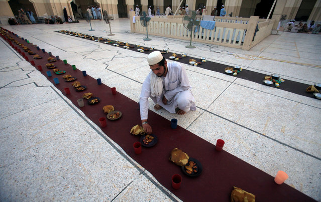 A man sets out food for fasters to break fast on the first day of the Muslim holy month of Ramadan in a mosque in Peshawar, Pakistan June 7, 2016. (Photo by Fayaz Aziz/Reuters)