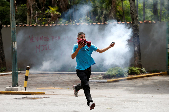 A demonstrator holds a tear gas canister as they clash with riot police officers during a protest called by university students against Venezuela's government in Caracas, Venezuela, June 9, 2016. (Photo by Carlos Garcia Rawlins/Reuters)