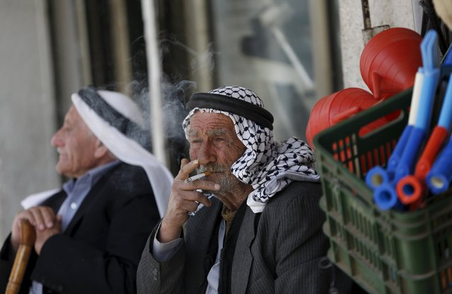 A Palestinian man smokes a cigarette at a market in the West Bank city of Ramallah March 25, 2015. (Photo by Mohamad Torokman/Reuters)