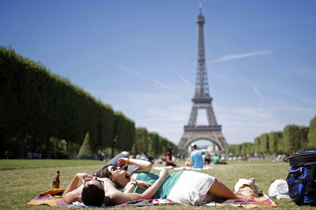 Tourists relax on the grass of the Champ de Mars in front of the Eiffel Tower in Paris, France, August 2, 2015 as warm summer temperatures return to the French capital. France has been the world's most visited country since the 1980's, welcoming 84 million tourists last year. (Photo by Stephane Mahe/Reuters)