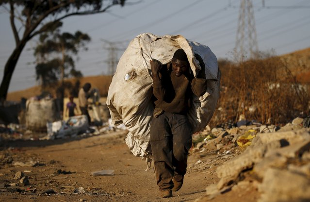 An unemployed man carries a bag full of recyclable waste material which he sells for a living, in Daveland near Soweto, South Africa August 4, 2015. (Photo by Siphiwe Sibeko/Reuters)