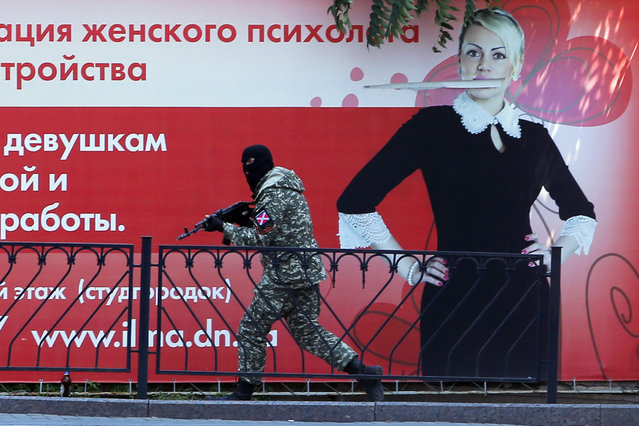 A pro-Russian fighter runs past a huge poster during fighting near a regional police department in downtown Donetsk, eastern Ukraine, Tuesday, July 1, 2014. Ukraine renewed its attacks against armed pro-Russian separatists Tuesday after the president called off a unilateral cease-fire, carrying out air and artillery strikes against rebel positions in eastern Ukraine. (Photo by Dmitry Lovetsky/AP Photo)