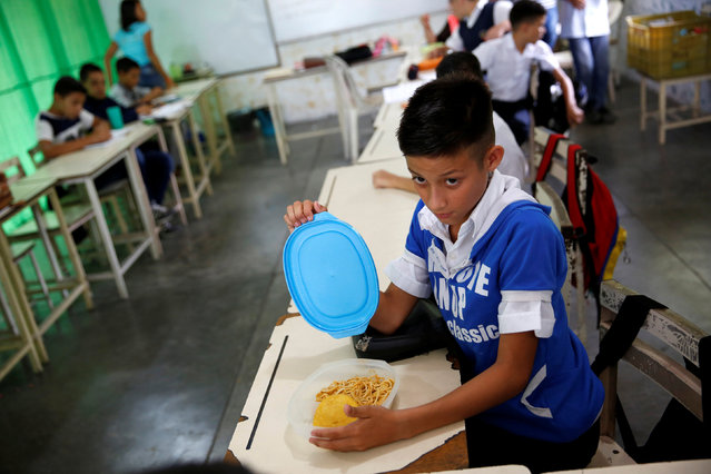 A child opens a container with a meal during a lunch break at an improvised classroom in a communal house, which is part of state school Monsenor Marco Tulio Ramirez Roa, in La Fria, Venezuela June 2, 2016. (Photo by Carlos Garcia Rawlins/Reuters)