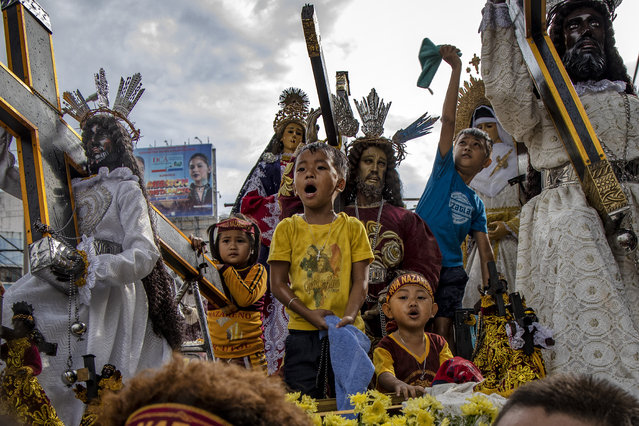 Children aboard a float carrying replicas of the Black Nazarene jubilate as they are doused with holy water, during a parade ahead of the Feast of the Black Nazarene, on January 7, 2020 in Manila, Philippines. The Feast of the Black Nazarene culminates in a day long procession on January 9 as barefoot devotees march to see and touch the image of the Black Nazarene. The Black Nazarene is a dark wood sculpture of Jesus brought to the Philippines in 1606 from Spain and considered miraculous by Filipino devotees. As many as 6 million devotees are expected to attend during the culmination in this predominantly Catholic nation in Southeast Asia. (Photo by Ezra Acayan/Getty Images)