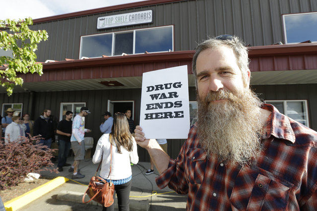 "Kevin Nelson, of Bellingham, Wash., holds a sign that reads ""Drug War Ends Here"", outside Top Shelf Cannabis, Tuesday, July 8, 2014, in Bellingham, Wash. on the first day of legal pot sales in the state. Nelson says he is a long-time activist opposing drug laws, particularly those targeting marijuana users, and he he feels the legalization of marijuana will lead to less crowded jails and be less of a burden on the court system. (Photo by Ted S. Warren/AP Photo)"