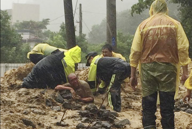 In this image released by the New Taipei Fire Department, emergency rescue personnel dig a man from a flash mudslide caused by Typhoon Soudelor in Xindian, New Taipei City, northern Taiwan, Saturday, August 8, 2015. (Photo by New Taipei Fire Department via AP Photo)