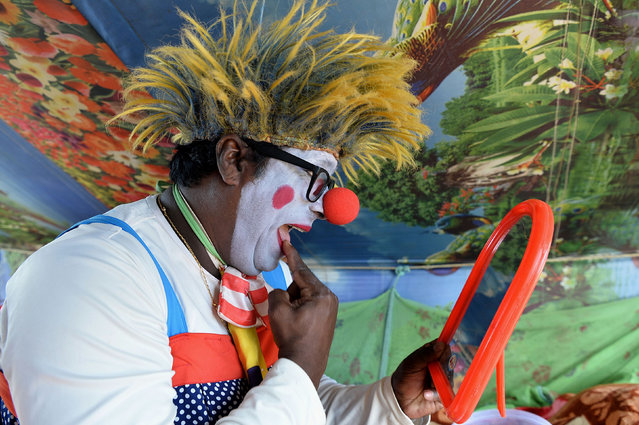 In this photo taken on July 11, 2017, Indian peformer Biju Nair, 45, gets ready in his clown costume before the Rambo Circus show in Bangalore. The 26- year- old Rambo Circus is among the very few surviving circus companies in India, touring the country and giving performances with its 160- strong troupe including 90 performing artists. (Photo by Manjunath Kiran/AFP Photo)