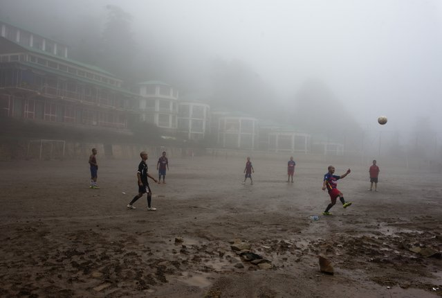 Exile Tibetan students play soccer in a school ground under heavy fog in Dharmsala, India, Sunday, August 9, 2015. The Himalayan region is seeing heavy rains and fog for the past few days. (Photo by Ashwini Bhatia/AP Photo)