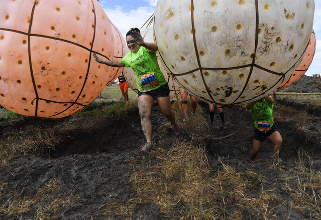 """Cara Horrigan, left, navigates the """"big balls"""" obstacle at MuckFest MS Denver July 15, 2017 at Salisbury North in Parker. Thousands of thrill-seekers braved the 5K obstacle course raising money for the National Multiple Sclerosis Society. The course included lots of mud, water and challenging obstacles including muddy tunnels, ponds, slides, ropes, swings, jumping into a large airbag and many others. Horrigan has MS, but that didn't stop her and her crew """"Cara's Muckers"""" from running the challenging course. (Photo by Andy Cross/The Denver Post)"""