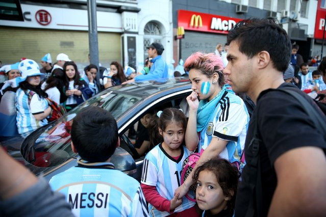 Argentine soccer fans gather around a car to listen to a radio broadcast of the second half of the World Cup final on July 13, 2014 in Buenos Aires, Argentina. (Photo by Joe Raedle/Getty Images)