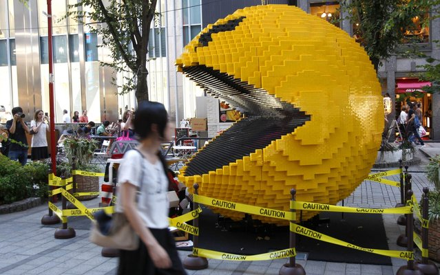 "A woman walks past a giant Pac-Man in Tokyo's Shinjuku area, Wednesday, August 12, 2015. The three-meter (about nine feet and 10 inches)-tall Pac-Man and other video game characters, made of Lego bricks, were on display to promote the upcoming movie ""Pixels"". (Photo by Ken Aragaki/AP Photo)"