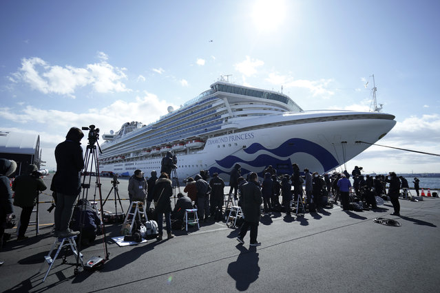 The cruise ship Diamond Princess is anchored at Yokohama Port for supplies replenished in Yokohama, south of Tokyo, Thursday, February 6, 2020. Health workers said 10 more people from the Diamond Princess were confirmed ill with the virus, in addition to 10 others who tested positive on Wednesday. They were dropped off as the ship docked and transferred to nearby hospitals for further test and treatment. (Photo by Eugene Hoshiko/AP Photo)