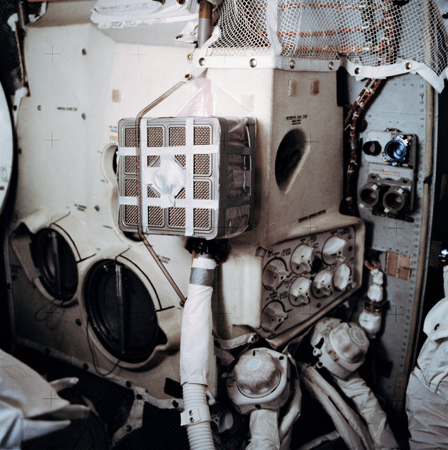 """Interior view of the Apollo 13 Lunar Module (LM) showing the """"mail box"""", a jury-rigged arrangement which the Apollo 13 astronauts built to use the Command Module (CM) lithium hydroxide canisters to purge carbon dioxide from the LM. Lithium hydroxide is used to scrub CO2 from the spacecraft's atmosphere. Since there was a limited amount of lithium hydroxide in the LM, this arrangement was rigged up to utilize the canisters from the CM. (Photo by NASA)"""