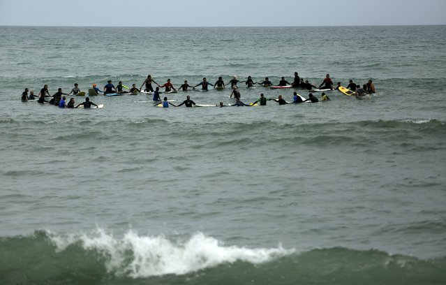 Surfers observe a minute of silence in memory of a cyclist who was killed by a car, during a protest in Lima, Peru, August 22, 2015. (Photo by Pilar Olivares/Reuters)