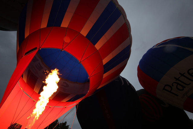 Hot air balloons are inflated in Queen Square ahead of the Bristol International Balloon Fiesta on August 5, 2014 in Bristol, England. Now in its 36th year, the Fiesta is Europe's largest annual hot air balloon event in the city that is seen by many as the home of modern ballooning.  (Photo by Peter Macdiarmid/Getty Images)