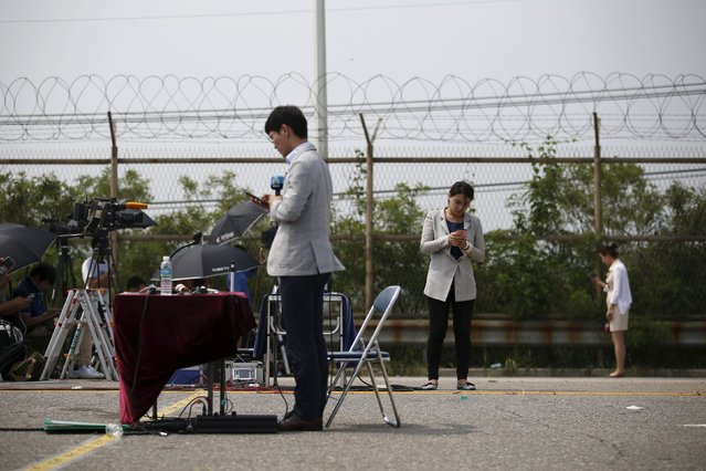 Reporters prepare for a report at a checkpoint on the Grand Unification Bridge which leads to the truce village Panmunjom, just south of the demilitarized zone separating the two Koreas, in Paju, South Korea, August 24, 2015. (Photo by Kim Hong-Ji/Reuters)