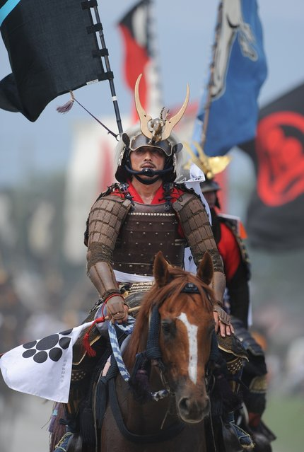 """A local man in samurai armor rides his horse during a parade at the annual Soma Nomaoi Festival in Minamisoma, Fukushima Prefecture, on July 29, 2012. Some 400 horses and thousands of people took part in the 1,000-year-old """"Soma Nomaoi"""", or wild horse chase, at the weekend in the shadow of Japan's crippled Fukushima nuclear plant. (Photo by Toru Yamanaka/AFP Photo)"""