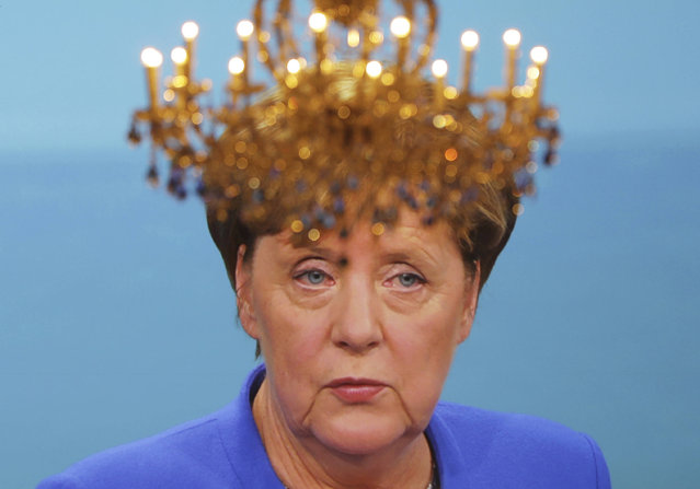 A chandelier sits in front of a screen showing German Chancellor Angela Merkel during the only TV debate between her and her Social Democratic challenger Martin Schulz before the German parliament election in Berlin Sunday, September 3, 2017. The German parliament election will be held Sept. 24, 2017. (Photo by Kay Nietfeld/DPA via AP Photo)