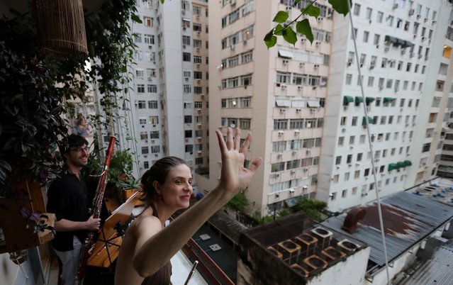 Classical musicians Sofia Ceccato and her husband Simon Bechemin acknowledge thanks as they play for neighbours from their balcony during the coronavirus disease (COVID-19) outbreak, in Rio de Janeiro, Brazil, March 21, 2020. (Photo by Sergio Moraes/Reuters)