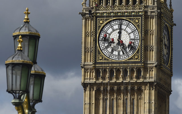 Cleaners abseil down one of the faces of Big Ben, to clean and polish the clock face, above the Houses of Parliament, in central London August 19, 2014. A week has been set aside for the cleaning of what is officially known as the Great Clock, which is set in the Elizabeth Tower. (Photo by Toby Melville/Reuters)
