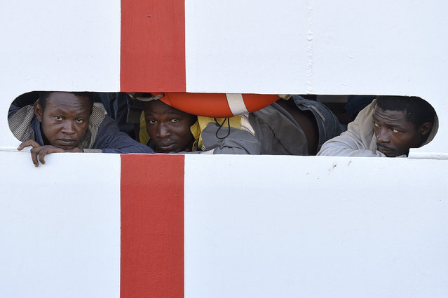 Migrants wait to disembark from Italian Coast Guard ship Diciotti at the Messina harbor in Sicily, Italy, Saturday, August 29, 2015. Migrants by the tens of thousands are braving the perilous journey across the Mediterranean, fleeing war and poverty in the Middle East, Africa and Asia with the hope of reaching Europe and be granted asylum. (Photo by Carmelo Imbesi/AP Photo)