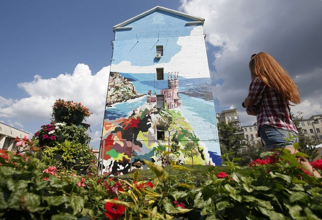 A woman walks past a mural on the side of a building which depicts the Swallow's Nest castle overlooking the Black Sea outside the Crimean town of Yalta, in Moscow, August 20, 2014. (Photo by Maxim Zmeyev/Reuters)
