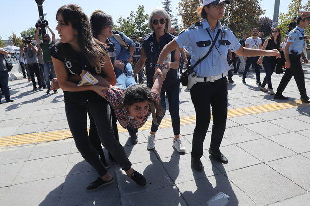 Riot police officers detain protesters during the trial of two Turkish teachers, who went on a hunger strike over their dismissal under a government decree following last year's failed coup, outside of a courthouse in Ankara, Turkey, September 14, 2017. Two imprisoned Turkish teachers who have been on a hunger strike for six months to protest their sacking in a mass purge went on trial today charged with terror-related offences. The case of academic Nuriye Gulmen and teacher Semih Ozakca, who have been jailed since May, has become a rallying cause for critics of the crackdown that followed the July 15 failed coup aimed at ousting President Recep Tayyip Erdogan. (Photo by Adem Altan/AFP Photo)