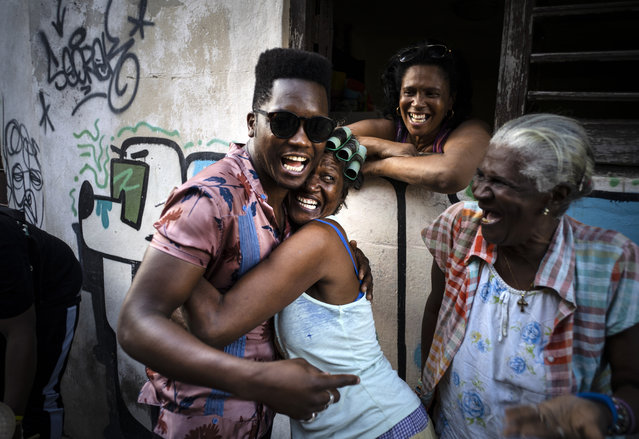 Cuban singer Cimafunk hugs a woman during the music conga through the streets of Old Havana within the activities of the 35th Havana Jazz Plaza festival in Havana, Cuba, Wednesday, January 15, 2020. (Photo by Ramon Espinosa/AP Photo)