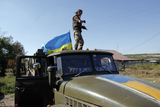 A Ukrainian serviceman stands on a military truck as he mans a checkpoint in Luhansk region August 20, 2014. (Photo by Valentyn Ogirenko/Reuters)