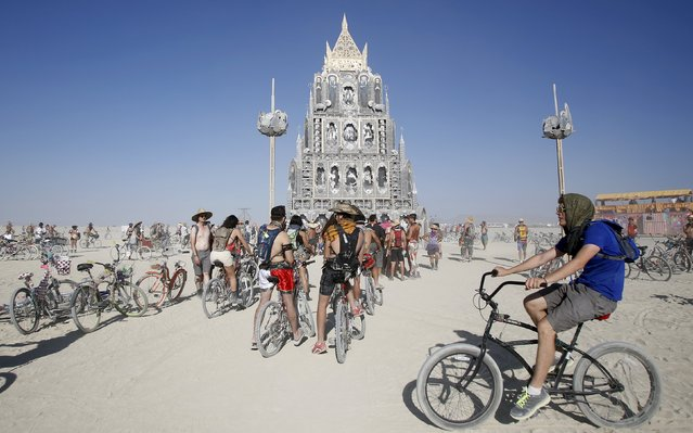 """Participants gather at the art installation """"Totem of Confessions"""" during the Burning Man 2015 """"Carnival of Mirrors"""" arts and music festival in the Black Rock Desert of Nevada, August 31, 2015. Approximately 70,000 people from all over the world are gathering at the sold-out festival to spend a week in the remote desert to experience art, music and the unique community that develops. (Photo by Jim Urquhart/Reuters)"""