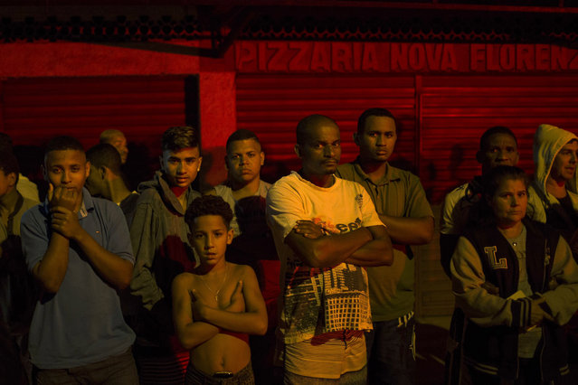 In this July 15, 2016 photo, residents watch as police work the crime scene where a man was murdered in Mage, greater Rio de Janeiro, Brazil. Scenes of impunity and violence play out daily in many of Rio's hundreds of slums, known here as favelas, and other outlying areas. The vast majority of killings are the result of heavily armed gangs who frequently shoot it out in turf wars. (Photo by Felipe Dana/AP Photo)
