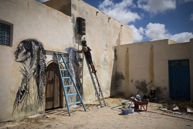 """US artist SWOON decorates a wall the village of Erriadh, on the Tunisian island of Djerba, on August 8, 2014, as part of the artistic project """"Djerbahood"""". (Photo by Joel Saget/AFP Photo)"""