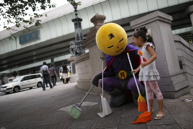 An unidentified man, who calls himself Mangetsu-man (Mr. Full Moon),  pauses as he cleans Nihonbashi bridge using a broom with a volunteer, while clad in a costume featuring a full moon for a head, in Tokyo August 25, 2014. (Photo by Issei Kato/Reuters)