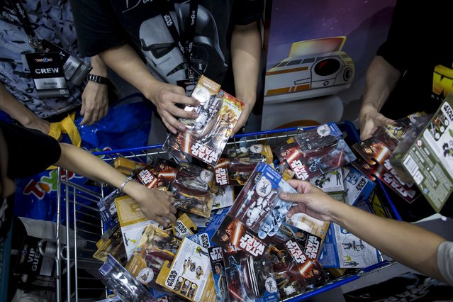 """Customers pick new toys from the upcoming film """"Star Wars: The Force Awakens"""" on """"Force Friday"""" in Hong Kong, China, September 4, 2015. (Photo by Tyrone Siu/Reuters)"""