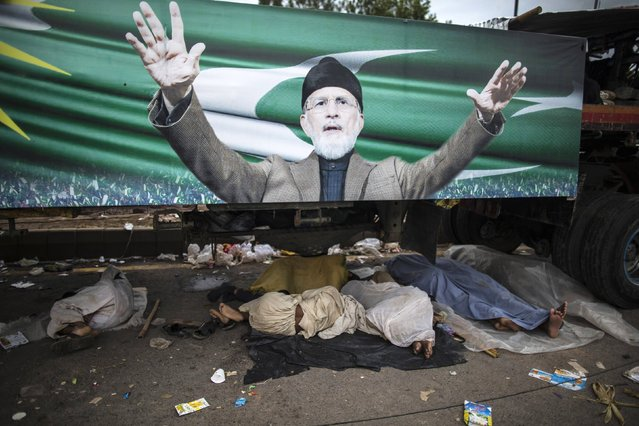 Anti-government protesters sleep under a truck with a poster of their leader Tahir ul-Qadri, Sufi cleric and leader of political party Pakistan Awami Tehreek (PAT), as they camp outside the parliament house during the Revolution March in Islamabad September 2, 2014. (Photo by Zohra Bensemra/Reuters)