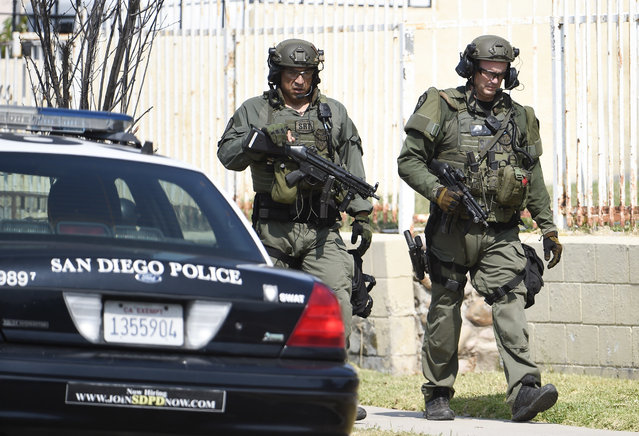 San Diego Police SWAT officers walk down the street after entering a house with a possible suspect inside Friday, July 29, 2016, in San Diego. One San Diego police officer was killed and another was wounded in a shootout following a late-night traffic stop, Friday night. A suspect was wounded and taken into custody a short time later and hours later police surrounded the home as they searched for man described as a possible accomplice. (Photo by Denis Poroy/AP Photo)