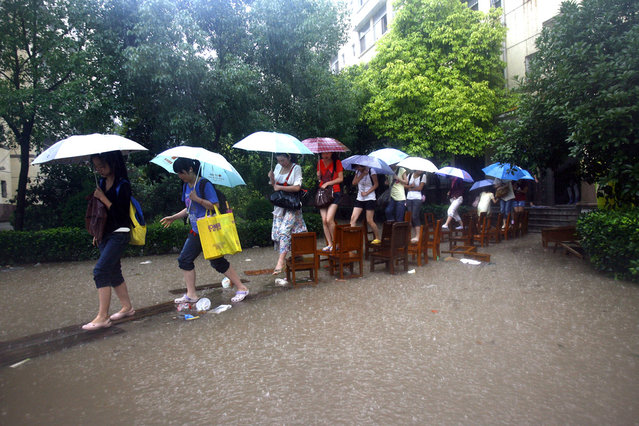 In a picture taken on June 18, 2011 Chinese students make their way across a flooded school compound walking along a row of chairs, in Wuhan, in central China's Hubei province on June 18, 2011. (Photo by AFP Photo)