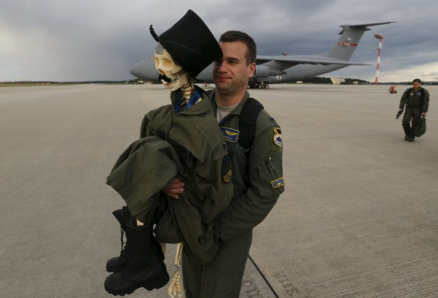 "Eric Kordus, a F-22 Raptor fighter jet pilot of the 95th Fighter Squadron from Tyndall, Florida, carries ""Mr. Bone"", the squadron's mascot consisting of a dressed-up plastic skeleton with a stovepipe hat and a moustache, after a refuelling mission of a KC-135 Stratotanker from the NATO airbase of Aemari, Estonia to Spangdahlem, Germany September 4, 2015. (Photo by Wolfgang Rattay/Reuters)"