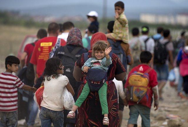Migrants walk on a dirt road after crossing the Macedonian-Greek border near Gevgelija, Macedonia, September 6, 2015. (Photo by Stoyan Nenov/Reuters)